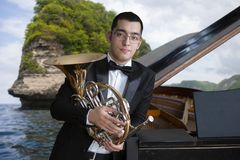 French horn player. Hornist playing brass orchestra music instrument. Portrait against the backdrop of the sea landscape. French horn player. Hornist playing royalty free stock image
