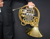 French horn player. Music instrument horn in the hands of hornist. A man in a suit with a musical instrument. stock photography