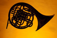 French Horn Silhouette Isolated on Yellow. A French horn silhouette isolated against a gold yellow background  in the horizontal format Royalty Free Stock Photos