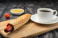 French Hot Dog and coffee on wooden table royalty free stock photo
