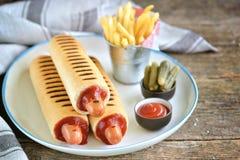 French hot dog with ketchup, mustard, mayonnaise and marinated cucumber. Royalty Free Stock Image