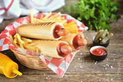 French hot dog with ketchup, mustard, mayonnaise and marinated cucumber. Stock Images