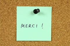 French language. Green small sticky note on an office cork bulletin board. Word thank you in French - merci stock photos