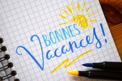 French language BONNES VACANCES! hand-lettered in notebook. French language BONNES VACANCES!  hand-lettered in notebook with brush calligraphy pens on wooden Royalty Free Stock Images