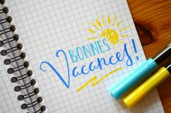 French language BONNES VACANCES! hand-lettered in notebook. French language BONNES VACANCES!  hand-lettered in notebook with brush calligraphy pens on wooden Stock Photo