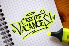 French language C`EST LES VACANCES! hand-lettered in notebook. French language C`EST LES VACANCES!  hand-lettered in notebook with brush calligraphy pen and Royalty Free Stock Photography