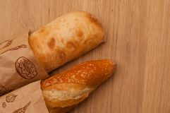 French loaf and Italian ciabatta on a wooden background royalty free stock images