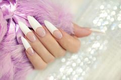 French long manicure. French long manicure is stackable with acrylic on a woman's hand on a brilliant background with fur stock photos