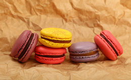 French macaron cookies on brown paper parchment. Group of several fresh colorful traditional French macaroon pastry cookies macarons, macaroni on brown paper Royalty Free Stock Photos