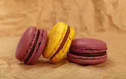 French macaron cookies on brown paper parchment. Group of several fresh colorful traditional French macaroon pastry cookies macarons, macaroni on brown paper Stock Photo