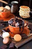 Tasty chocolate ice cream in cup on wooden table. French macarons and chocolate ice cream with sweet sauce. Selective focus royalty free stock image