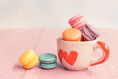 French macarons in cup on pink wooden background.Toned image Royalty Free Stock Photos