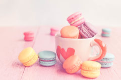 French macarons in cup on pink wooden background.Toned image Stock Photography