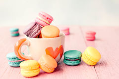 French macarons in cup on pink wooden background.Toned image Royalty Free Stock Photo