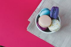 French macarons in cup. Sweet colorful bisquits. Top view. Hot pink background. Table cloth. Stock Images