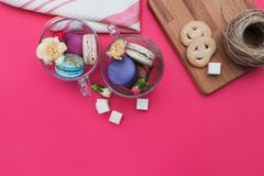 French macarons in glass cup with flowers and sugar on the pink background. Wooden desk with cookies. Top view. Stock Photos