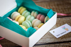 French macarons, mix colors in a box. On wood background Royalty Free Stock Photos