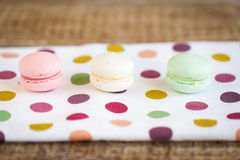 French macarons, mix colors. On a fabric with multi color dots Stock Photography