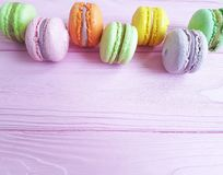French macaroon on a pink wooden sweet biscuit. French macaroon on a pink wooden delicious sweet biscuit Stock Image