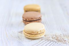 French macaroons close up: vanilla,mocca,chocolate. On white wooden background Stock Images