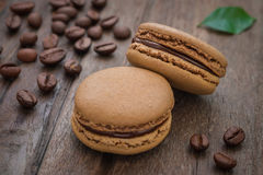 French macaroons and coffee beans on wooden table Royalty Free Stock Photos