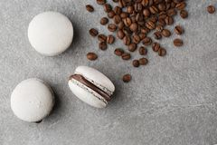 French macaroons  with coffee beans. Selective focus. macaroon in gray tone. Three beautiful macaroons on gray royalty free stock image