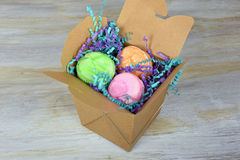French macaroons in take out box. Colorful macaroons in brown generic take out container on whitewashed wood Stock Photo