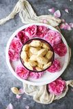 French Madeleine cookie with rose petals. French Madeleine - soft butter cookies made in special mold. Served with rose petals royalty free stock images