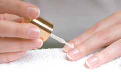 French Manicure 2. Close-up of hands doing French manicure. Focus is near the brush on the middle finger of the painted hand Royalty Free Stock Photography