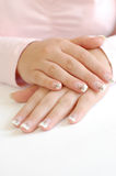 French Manicure. Closeup of young woman with crossed hands and beautiful long manicured nails Royalty Free Stock Photography