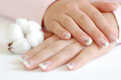 French Manicure. Closeup of young woman with crossed hands and beautiful long manicured nails with a cotton boll on the side Royalty Free Stock Photos