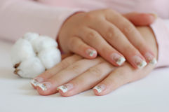French Manicure. Closeup of young woman with crossed hands and beautiful long manicured nails with a cotton boll on the side Royalty Free Stock Photography