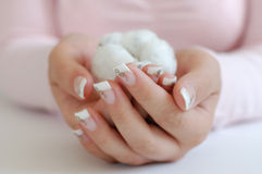 French Manicure. Young woman with beautiful long nails holding a cotton boll Royalty Free Stock Photos