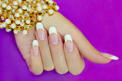French manicure. French manicure with a beautiful decoration on the wrist of the lilac background stock image