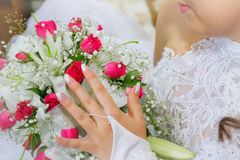 French manicure with a bouquet BRIDE. French Manicure - Woman holds a bouquet of pink roses and shows off her french manicured fingernails Stock Photos