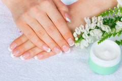 French manicure. Female hands with french manicure near jar of cream stock images