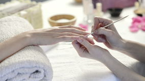 French manicure at spa center. Closeup shot of a woman using a cuticle pusher to give a nail manicure. Nail technician giving customer a manicure at nail salon stock video footage