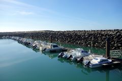 French Marina with Large Break-wall. This is a boat harbor on the Atlantic coast in France with small motor boats sheltered by a giant breakaway of piled stone Royalty Free Stock Images