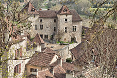 French Medieval Courtyard. Quaint French Medieval courtyard surrounded by thick stone buildings with clay tile roofs in the heart of Saint Cirq Lapopie Royalty Free Stock Image