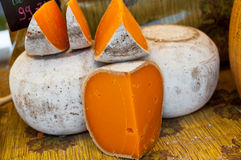 French mimolette cheese. Pieces of traditional French mimolette cheese for sale at farmers market royalty free stock photos