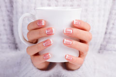 French moon manicure. Female hands with beautiful manicure hold white cup. French moon manicure royalty free stock photography