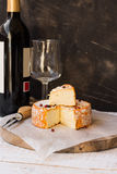 French munster cheese with orange rind, red pepper corns, cut off slice, fork,wine bottle and glass Stock Image