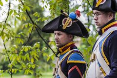 French napoleonic soldiers are preparing themselves for the battle. Two sargent of the french napoleonic army are standing and watching to their captain not in Royalty Free Stock Photos