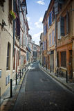 French narrow street. Vertical wide angle view of a narrow street in Toulouse, France Stock Image