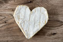 French Neufchatel cheese shaped heart on a wooden table Royalty Free Stock Photo