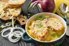 French onion gratin soup. With cheese and toast. Delicious homemade soup in bowl, ingredients on board on old wooden table royalty free stock image