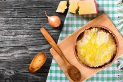 French onion gratin soup in a clay pot, authentic recipe, wooden spoon on a cutting board on an old rustic table, close-up Stock Image