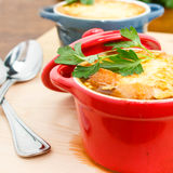 French Onion Soup Gratin. In red and blue pots on table top Stock Image