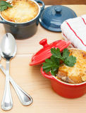French Onion Soup Gratin. In red and blue pots on table top Royalty Free Stock Image