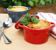 French Onion Soup Gratin. In red and blue pots on table top Stock Photo